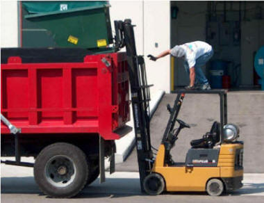 danger standing on forklift emptying bin in dump